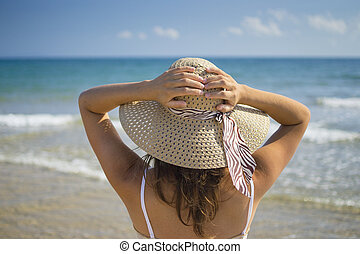 Beautiful young woman gently holds her summer hat whilst looking out to sea