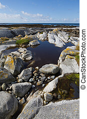 Looking out to sea over the Rocks and rock pools in South Uist in the Outer Hebrides