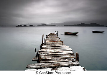 Looking over a desolate pier and a boat
