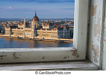 Looking through a castle window, the view of Buda in the foreground with the Hungarian Parliament building on the Pest side of Budapest in the background.