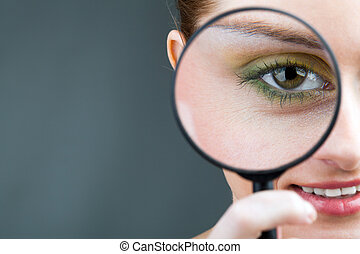 Looking through magnifier - Close-up of young woman looking...