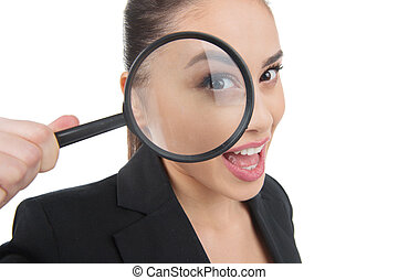 Looking through magnifying glass. Beautiful young woman looking through the magnifying glass and smiling while isolated on white