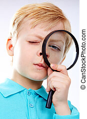 Looking through magnifying glass - Portrait of a kid looking...