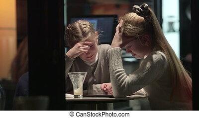 Looking through night window at two teen girls in coffee shop