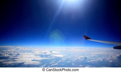 Looking through window aircraft during flight in wing with a nice blue sky and sun. HD. 1920x1080