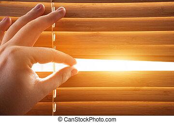 Looking through window blinds, sun light coming inside. ...