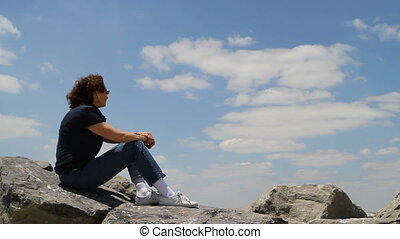 Looking To Future Concept - Woman sitting on rocks with her...