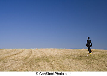 Looking to the future - businessman in a field looking high ...