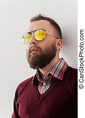 Looking trendy. Handsome young man in sunglasses leaning at the wall and looking away
