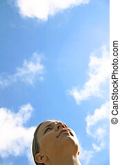 A young woman looking up into the sky.