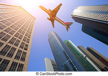 Looking up at aircraft flying over the modern urban office buildings backgrounds at Shanghai