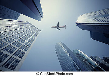 Looking up at aircraft flying over the modern urban office...