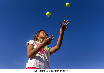 Looking up at girl juggling. - A girl tries juggling against...
