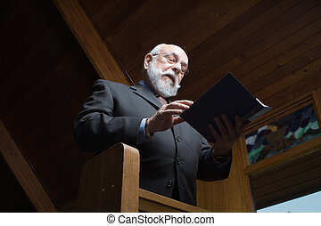 Looking up at Senior Man Singing Hymn in Church Pew