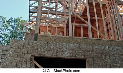 Looking up at new construction beams under a clear blue sky with sunlight