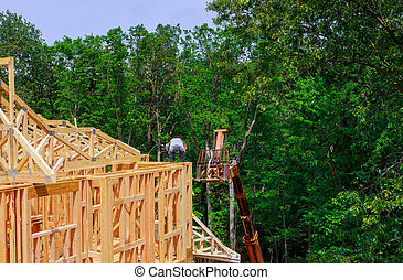 Looking up new construction beams under a clear blue sky with sunlight