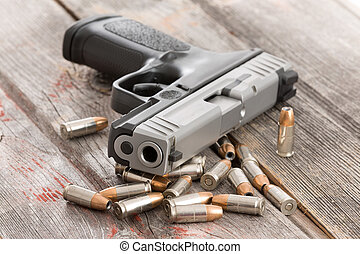 Looking up the muzzle of a handgun surrounded by scattered bullets and ammunition lying on old rustic wooden boards conceptual of violence, killing, crime and burglary