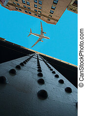 Looking up view of cast iron buildings in New York City with an airplane over a blue sky.