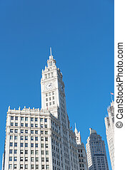 Low angle view top of traditional building with a clock faces pointing in all directions. Clock tower along Michigan Avenue in downtown Chicago, Illinois.