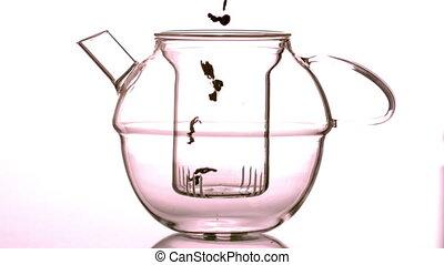 Loose tea falling into glass teapo - Loose tea falling into...
