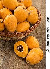 Loquat Medlar fruit on wooden background.