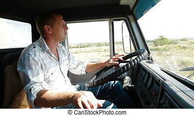 Lorry driver at the wheel of truck on country road