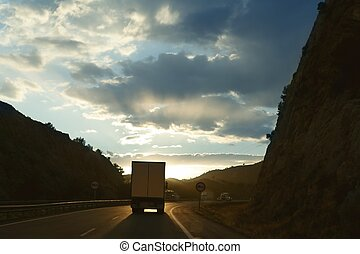 Lorry truck backlight on a golden Europe road evening