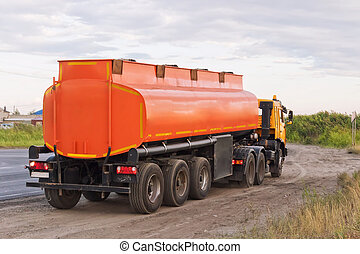 Lorry with orange tanker on parked on the roadside of a...