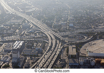 Smoggy afternoon aerial view of Harbor 110 and Santa Monica 10 freeways in downtown Los Angeles, California.