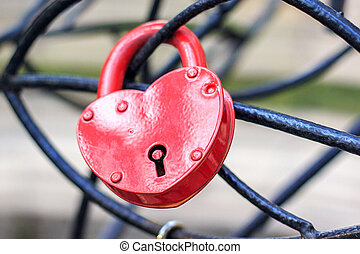 ?losed red lock in the form of a heart hangs on an iron structure.