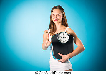 Losing weight - Young woman with measuring scale