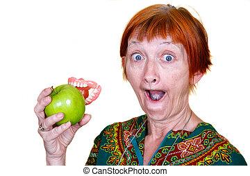 Elderly lady losing her teeth on a bite of an apple