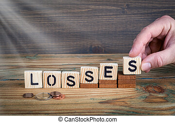 losses. Wooden letters on the office desk, informative and communication background