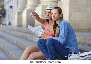 lost and confused girl friends looking for directions on map