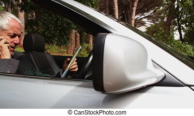 Lost businessman reading map and talking on phone in his car