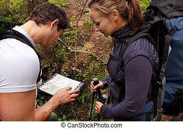 Lost Camping Couple - A coupld with map and compass in the...