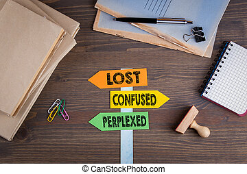 Lost, confused and perplexed concept. Paper signpost on a wooden desk