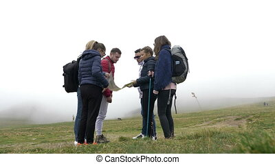 Lost group of teenage friends checking the map trying to...