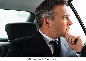 Lost in business thoughts. Thoughtful mature businessman holding hand on chin and looking away while sitting on the back seat of a car
