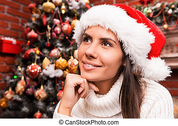 Lost in Christmas thoughts. Thoughtful young woman in Santa hat holding hand on chin and looking away while sitting in front of the Christmas Tree