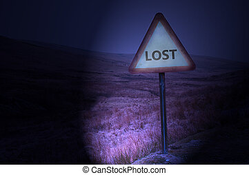 Night shot of a single road warning sign with the word 'lost' illuminated by car headlights with subtle remote and dark landscape behind.