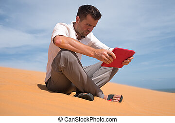 Lost in the desert. Caucasian man sitting on sand with tablet. He is lost and lookking in map where to go