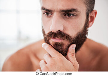 Lost in thoughts. Portrait of thoughtful young bearded man holding hand on chin and looking away