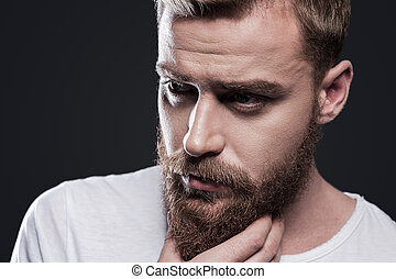 Lost in thoughts. Portrait of thoughtful young bearded man looking away and holding hand on chin while standing against grey background