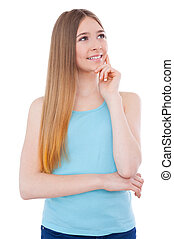 Lost in thoughts. Thoughtful teenage girl holding hand on chin and looking away while standing isolated on white