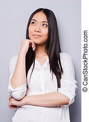 Lost in thoughts. Thoughtful young Asian woman holding hand on chin and looking away while standing grey background