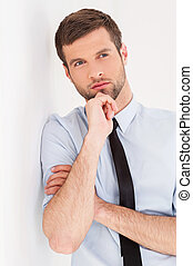 Lost in thoughts. Thoughtful young man in shirt and tie looking away and holding hand on chin while leaning at the wall