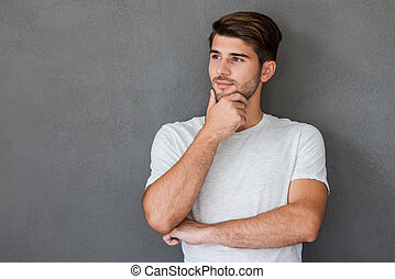 Lost in thoughts. Thoughtful young man holding hand on chin and looking away while standing against grey background