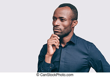 Lost in thoughts. Thoughtful young African man holding hand on chin and looking away while standing against grey background