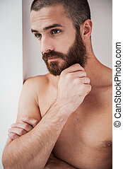 Lost in thoughts. Thoughtful young bearded and shirtless man holding hand on chin and looking away while leaning at the wall